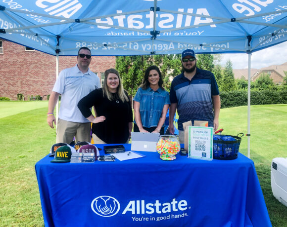 Allstate employees posing under an Allstate tent at Foxland golf course