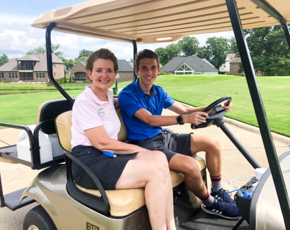 2020 President Shellie Tucker and her nephew on a golf cart at Foxland golf course