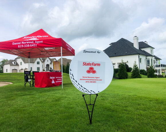 State farm sponsorship sign and tent at Foxland Golf course