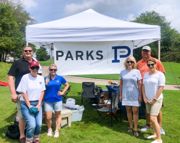 Parks employees posing with their tent at Foxland golf course