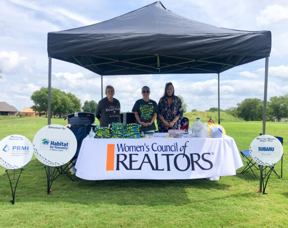 Employees of Women's Council of Realtors and Habitat for Humanity of Sumner County posing under a tent at Foxland golf course